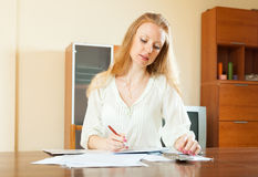Serious long-haired woman fills in financial documents Royalty Free Stock Photography