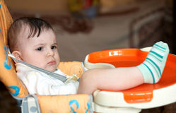 Serious look. Year-old boy with a very serious expression crossed his chair for feeding Royalty Free Stock Photography