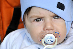Serious looking baby with dummy. In mouth Royalty Free Stock Photo