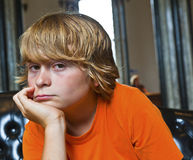 Serious looking boy sitting on a sofa Royalty Free Stock Image