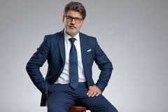 Serious looking businessman holding his hand in his pocket. While wearing a blue suit and sitting on a stool on gray studio background royalty free stock image