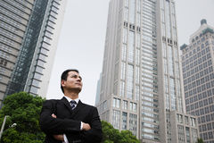 Serious looking businessman near skyscrapers Stock Photography
