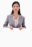 Serious looking businesswoman with blank sign board Stock Photos