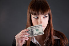 Serious looking businesswoman with dollars. Studio shot Royalty Free Stock Photo