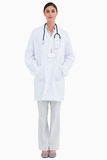 Serious looking doctor with hands in her pockets Royalty Free Stock Image