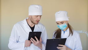 Serious looking doctors consulting something over tablet computer stock video