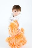Serious looking girl standing with big orange furr Stock Photography