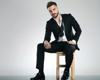 Serious looking guy staring to the camera. And wearing a black tuxedo while sitting on a chair on gray studio background royalty free stock photos