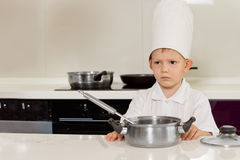 Serious looking little chef in the kitchen Royalty Free Stock Photo