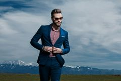 Serious looking man adjusting his jacket and walking royalty free stock images