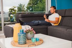 Serious looking man texting with his phone and chilling on the couch stock photos