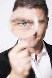 Serious looking man watching with magnifying glass Royalty Free Stock Images