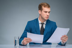 Serious-looking newscaster reading his papers Royalty Free Stock Photo
