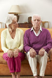 Serious Looking Senior Couple Sitting On Sofa At Home Royalty Free Stock Image