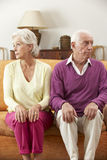 Serious Looking Senior Couple Sitting On Sofa At Home Royalty Free Stock Photography