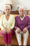 Serious Looking Senior Couple Sitting On Sofa At Home Royalty Free Stock Photos