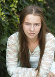 A serious looking teen girl with long brown hair and lace blouse. Royalty Free Stock Photo