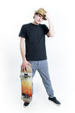 Serious looking teenager sitting on skate. Isolated on white background Royalty Free Stock Photography