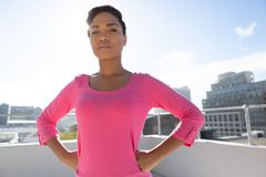 Serious looking woman standing confident for breast cancer awareness. In pink shirt against urban background royalty free stock photo