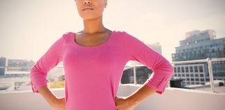 Serious looking woman standing confident for breast cancer awareness. In pink shirt against urban background royalty free stock photography