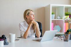Serious looking woman thinking about something at workplace. Serious looking business woman thinking about something at workplace royalty free stock photo