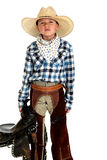 Serious looking young cowboy holding a saddle in c. Serious looking young cowboy holding a saddle stock photography