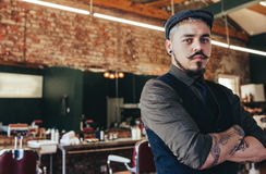 Serious looking young man standing at barber shop Royalty Free Stock Images