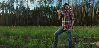 Serious Lumberjack in a Forest. Serious Lumberjack with a big Ax on Shoulder in a Forest Royalty Free Stock Photo