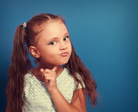 Serious makeup thinking kid girl with long hair looking on blue Royalty Free Stock Photo