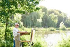 Serious male artist holding brush and painting picture on easel on open air. stock images