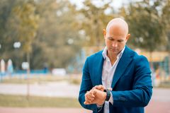 Serious male entrepreneur in formal suit looking at wristwatch planning working schedule , confident executive manager. Serious male bald entrepreneur in formal Stock Image