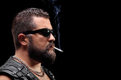 Serious male biker smoking a cigarette Royalty Free Stock Images