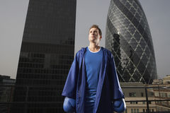 Serious Male Boxer Against Skyscrapers In London. Serious male boxer standing in front of downtown skyscrapers in London Stock Images