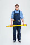 Serious male builder holding waterpas Royalty Free Stock Photography