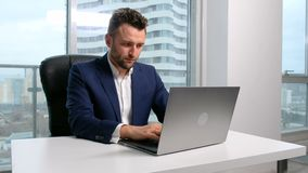 Businessman typing on the laptop in office. Serious male businessperson in costume sit in room, look at monitor of desktop pc on the desk, type letter to the stock video footage