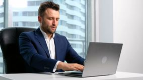Businessman typing on the laptop in office. Serious male businessperson in costume sit in room, look at monitor of desktop pc on the desk, type letter to the stock footage