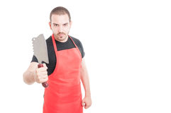 Serious male butcher showing meat chopper Royalty Free Stock Photo
