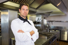 Serious male cook with arms crossed in kitchen Stock Photography
