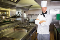 Serious male cook with arms crossed in the kitchen Royalty Free Stock Photos