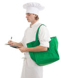 Serious male cook writing on clipboard Stock Photos