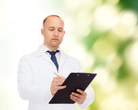 Serious male doctor with clipboard Stock Photography
