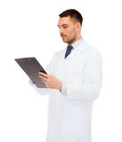 Serious male doctor with clipboard Stock Image