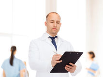 Serious male doctor with clipboard Royalty Free Stock Image