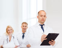 Serious male doctor with clipboard Royalty Free Stock Photography