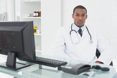 Serious male doctor with computer at medical office Royalty Free Stock Photography