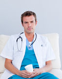 Serious male doctor drinking coffee Stock Photography