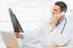 Serious male doctor examining xray while on call Stock Photo