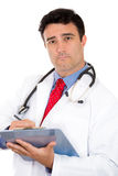 serious male doctor or healthcare professional or nurse wearing red tie and stethoscope writing on clipboard Royalty Free Stock Image