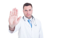 Serious male doctor showing stop gesture with one hand Royalty Free Stock Image