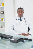 Serious male doctor sitting with computer at medical office Stock Photos